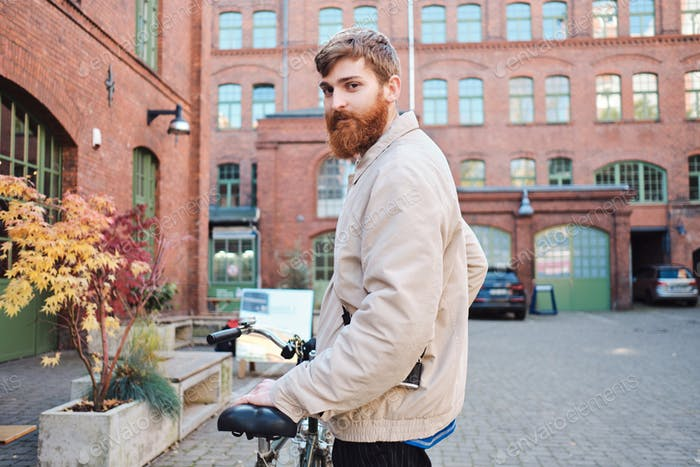 Young attractive bearded man with bicycle intently looking in camera on city street