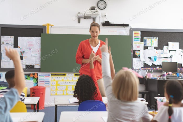 School kids raising hand to answer the teacher question in classroom