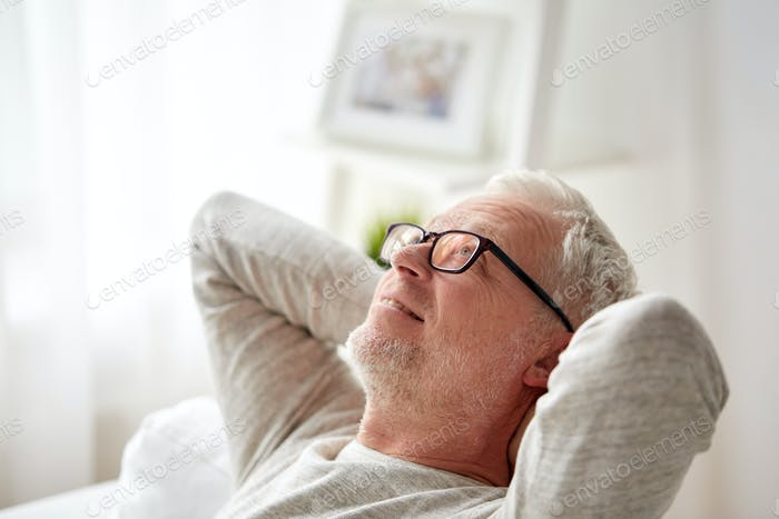 smiling senior man in glasses relaxing on sofa