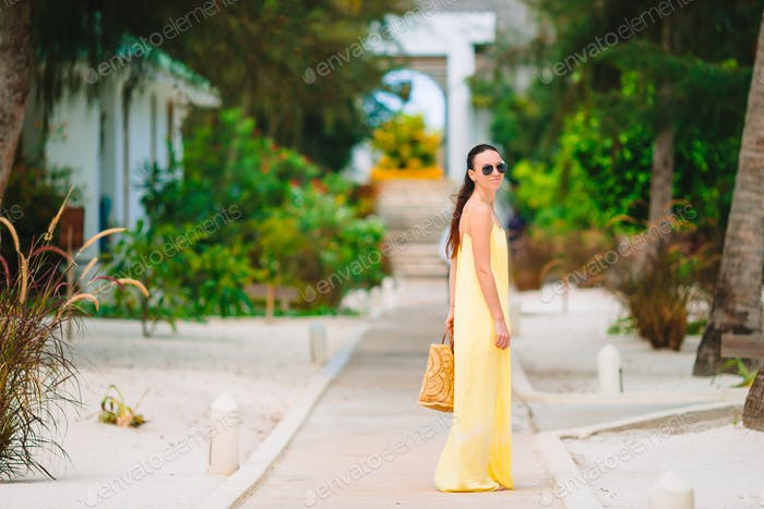 Young woman during tropical beach vacation. Back view of happy girl enjoying her holidays
