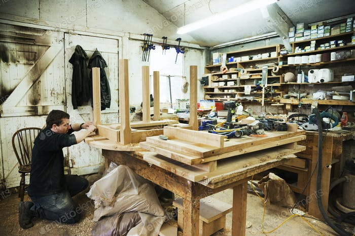 Man standing in a carpentry workshop, working on the skirting of a wooden table.