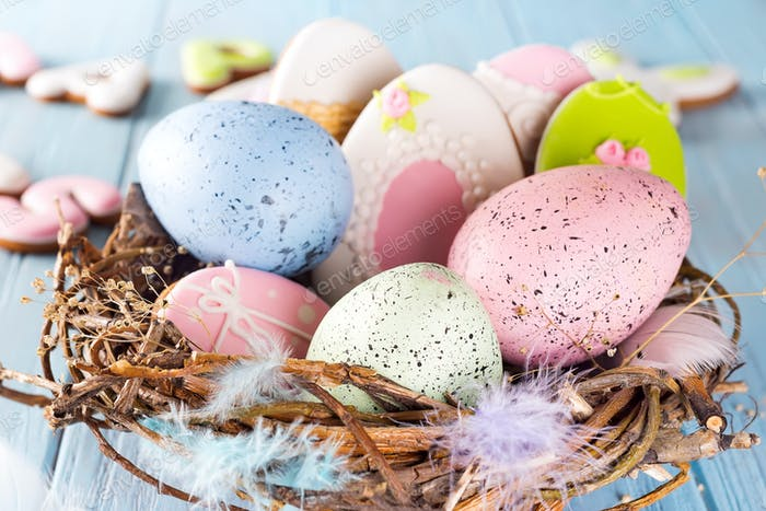 Colorful easter eggs cookies and easter eggs in wooden nest on blue wooden background, close up