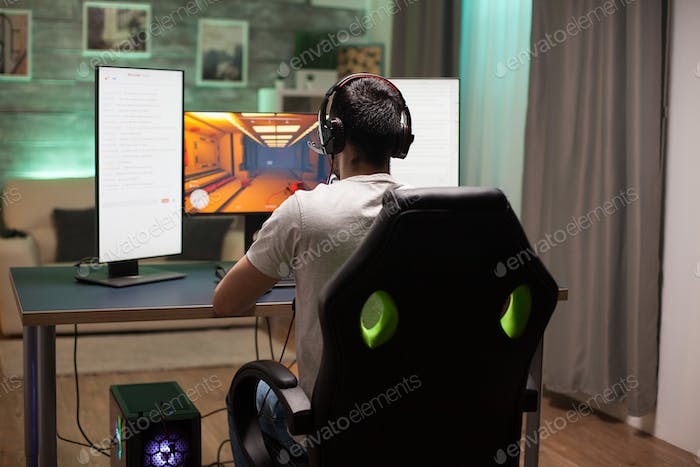 Back view of man sitting on gaming chair