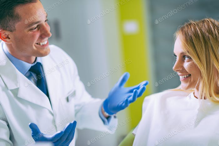 Young Dentist Talking to Satisfied Patient