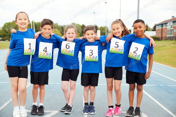 Portrait Of Children On Athletics Track Wearing Competitor Numbers On Sports Day