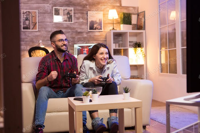 Happy young couple after winning at video games on television