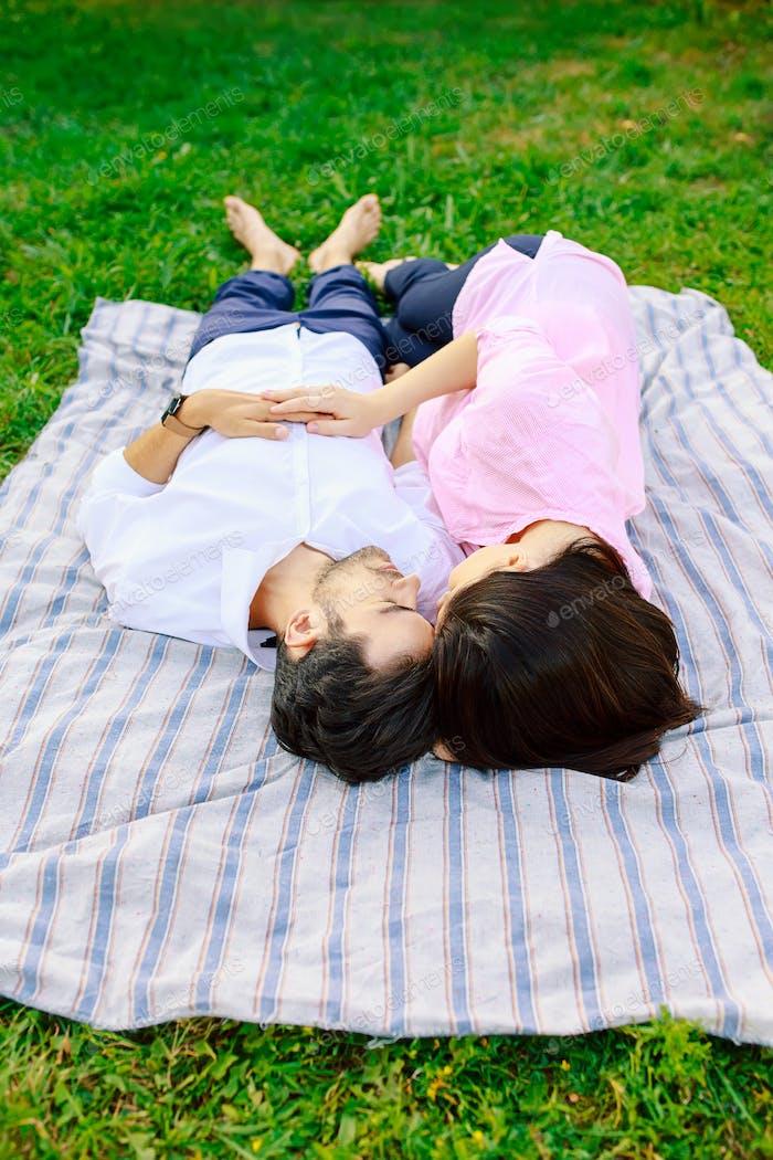 Young loving couple lying together enjoying closeness