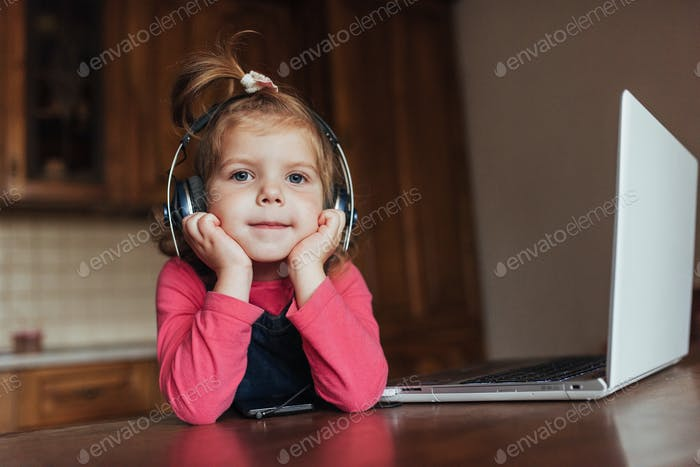 Happy beautiful child in headphones listening to music