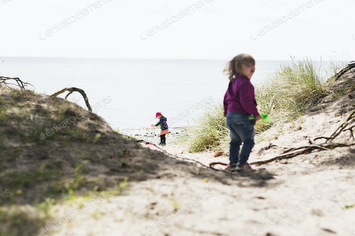 Children playing on field by sea