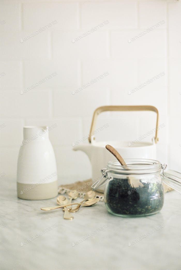 Teekanne, Krug und ein Glas mit schwarzen Teeblättern.