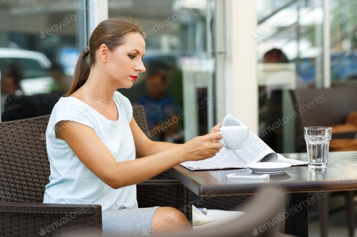 Young woman reading a newspaper and drinking morning coffee in a