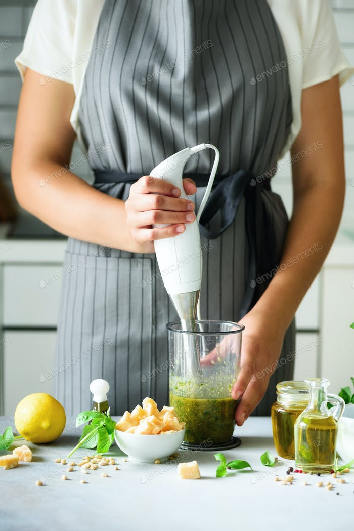 Woman using hand blender to make pesto. White kitchen interior design. Copy space. Vegetarian, clean