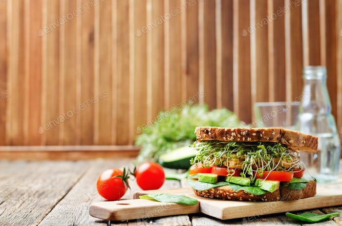 sprouts avocado tomato spinach chickpeas burger rye sandwich