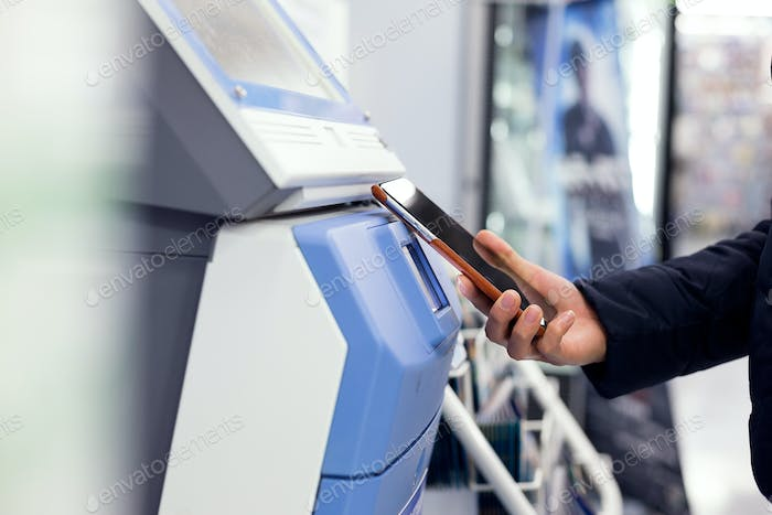 Woman connecting cellphone and ticketing machine