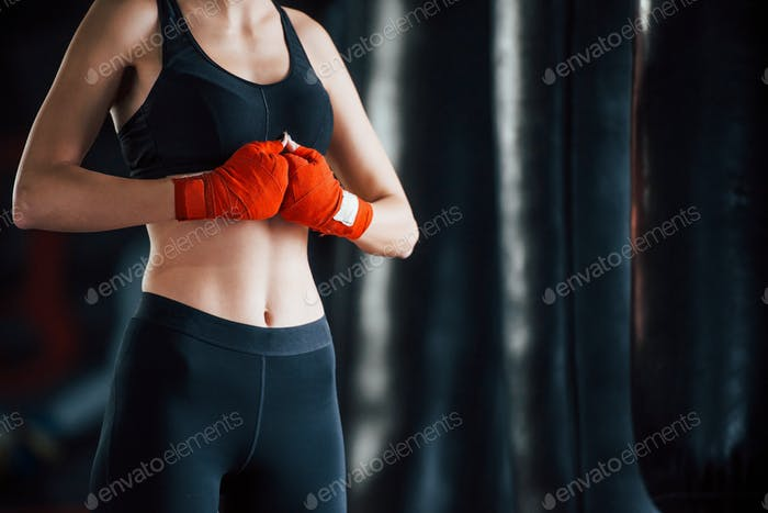 Young woman in sportive wear is in the gym having exercise day. Conception of boxing