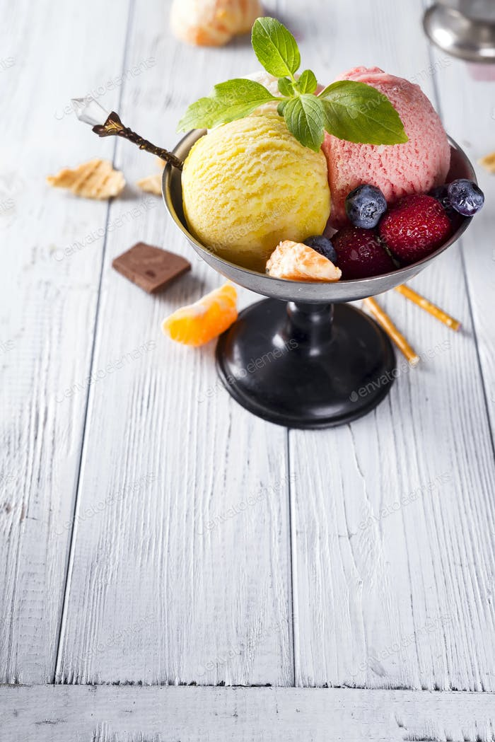 Bowl with ice cream with three different scoops of yellow, red colors and waffle cone, chocolate,