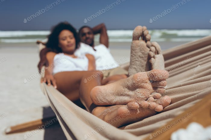 Couple relaxing on hammock at beach