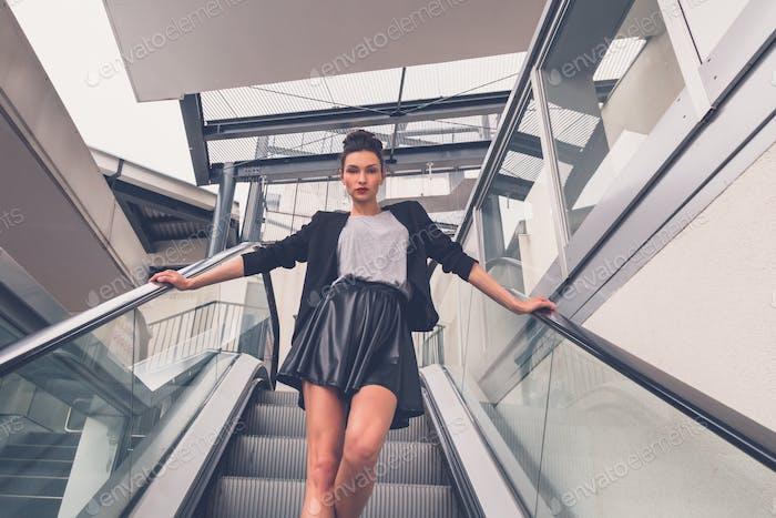 Beautiful girl posing on an escalator