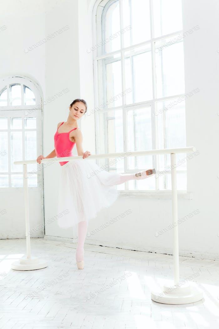 Ballerina posiert in Spitzenschuhen im weißen Holzpavillon
