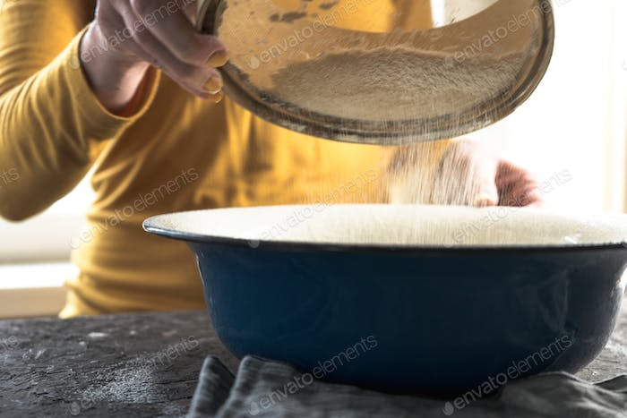 White flour is sieved in a large blue bowl