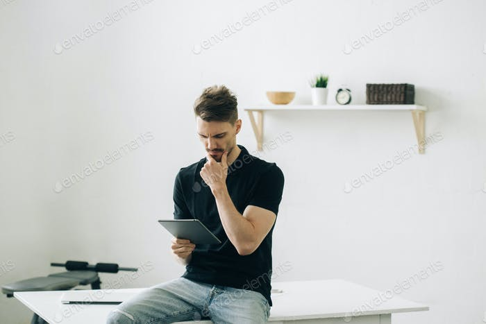 Man with tablet indoors portrait. Male portrait with tablet home