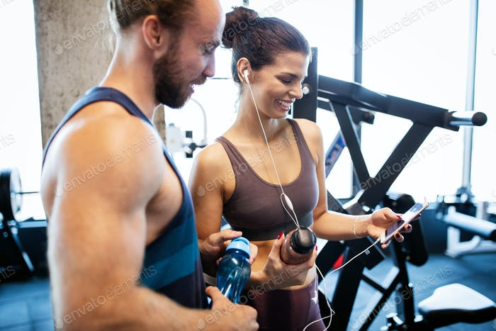 Junge sportliche Frau zeigt etwas auf Smartphone zu ihrem männlichen Freund in ein Fitness-Studio