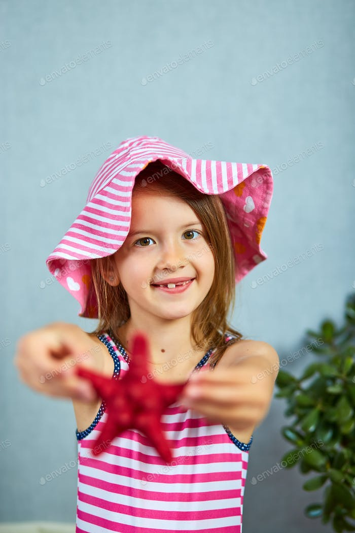 Smiling little girl wearing pink hat holding starfish.
