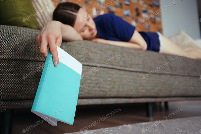 Woman got asleep while reading on sofa in the living room