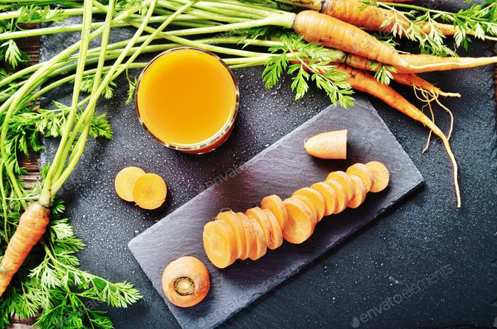 Top view at fresh organic vegetarian Carrot juice on wooden kitc