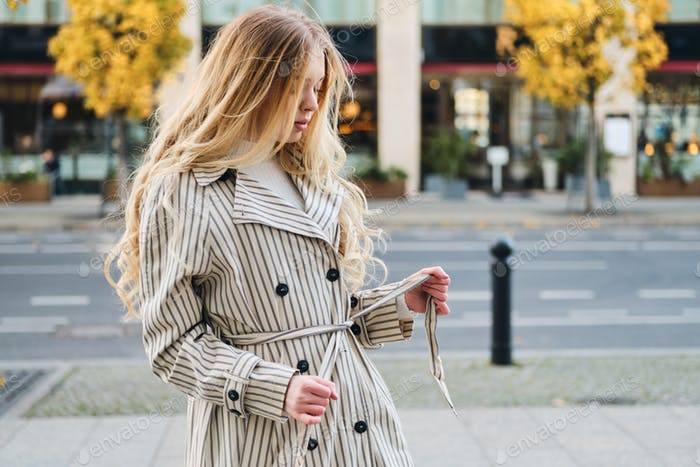Gorgeous blond girl in stylish trench coat walking around city street