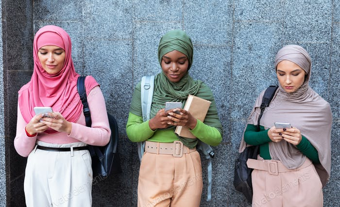 Three Modern Muslim Women Using Cellphones Standing Over Gray Wall