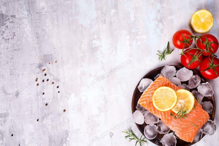 Filetes de salmón sobre Hielo con rodaja de limón sobre plato de De madera con tomate