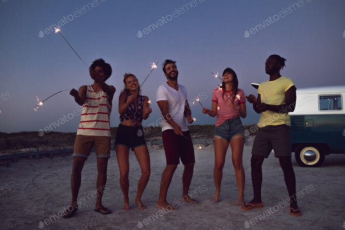 Front view of happy group of diverse friends playing with sparklers on the beach at dusk
