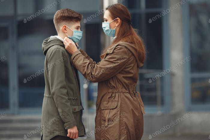 A boy and mother are wearing protective masks