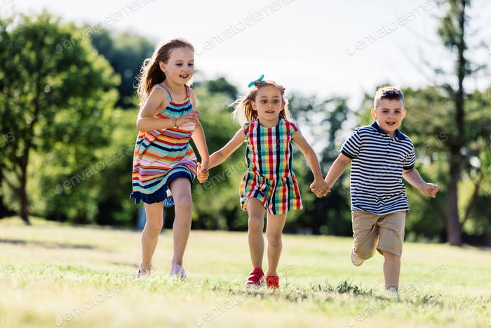 Two little girls and a boy running on the grass field.