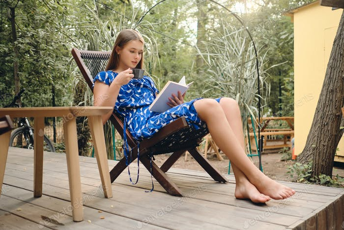 Beautiful brown haired girl in dress barefoot drinking coffee reading book on wooden chair in park