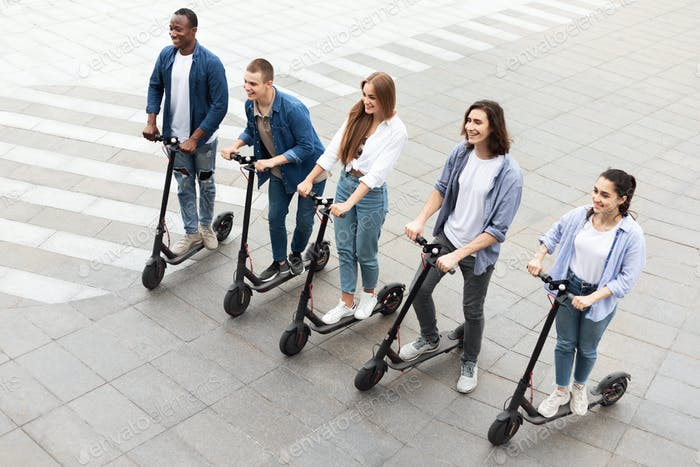 Five friends having ride on electric kick scooters