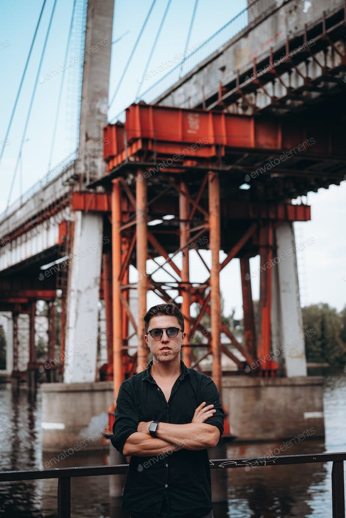 Guy in sunglasses on the background of the bridge