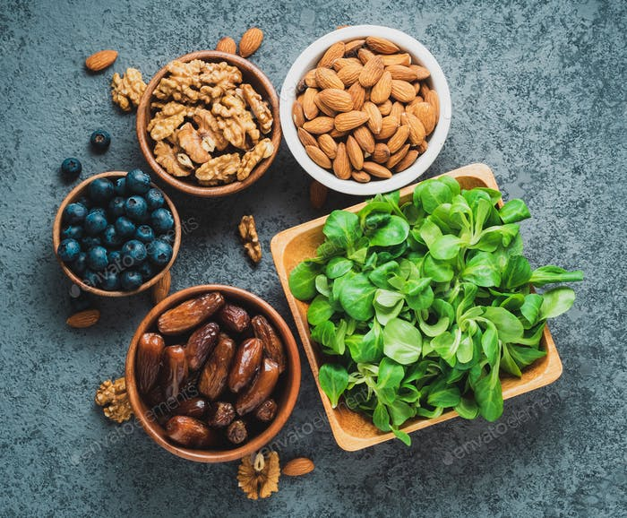 Healthy vegan food - dry fruits, greens, nuts, berry. Superfoods on gray stone background, top view.