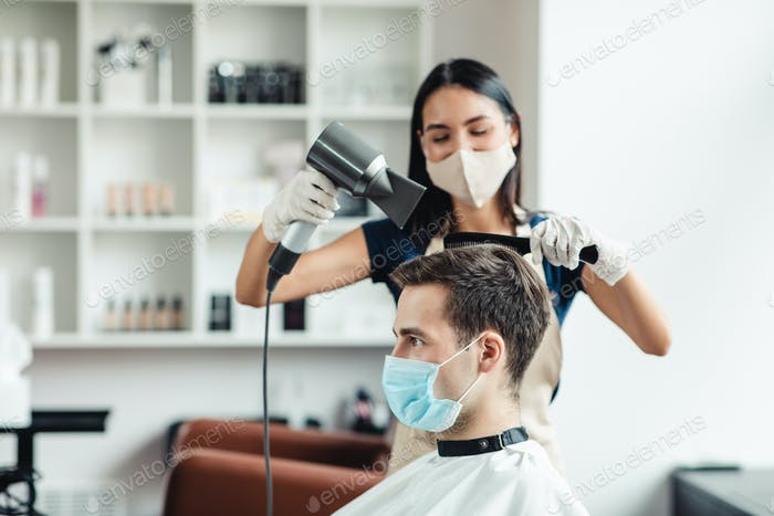 Hairdresser making trendy hairstyle for young man, both in protective masks