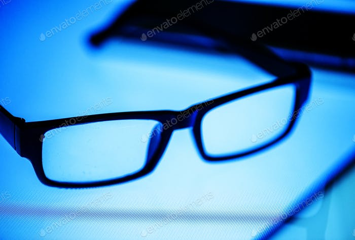 Eyeglasses on a digital desk