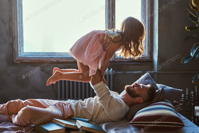 Dad and daughter in bed. Father playing with adorable daughter in bedroom.