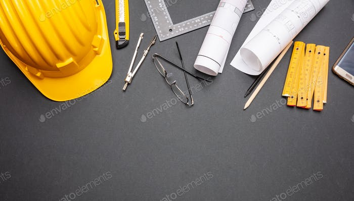 Thumbnail for Project blueprints, yellow hardhat and engineering tools on black
