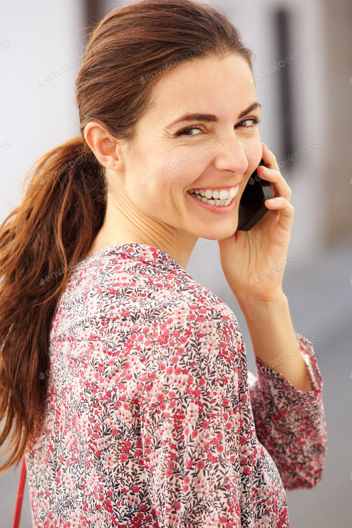Close up beautiful young woman talking on cellphone and smiling outside