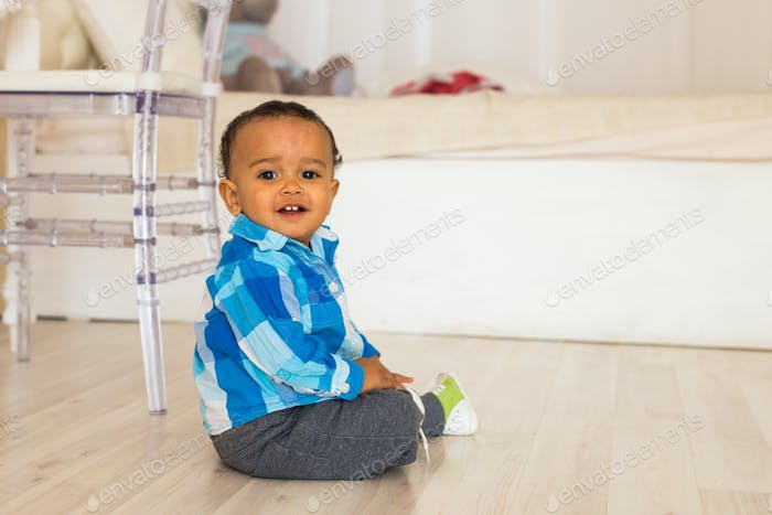 Full length portrait of a young mixed race boy sitting on the floor.