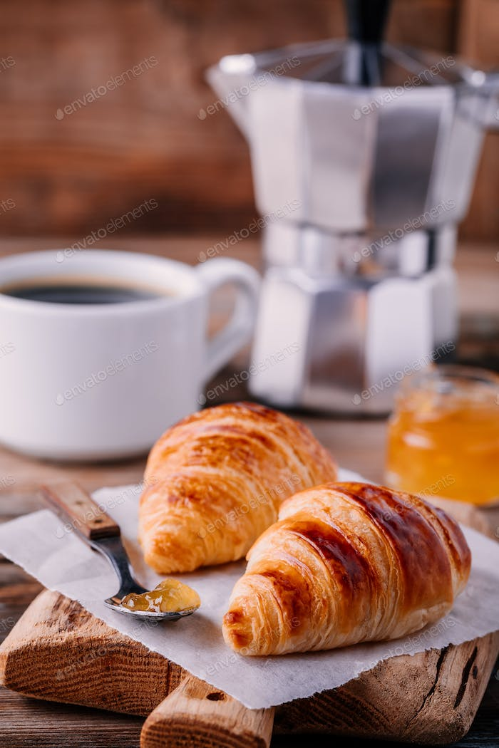 Homemade baked croissants with jam and coffee on wooden rustic background