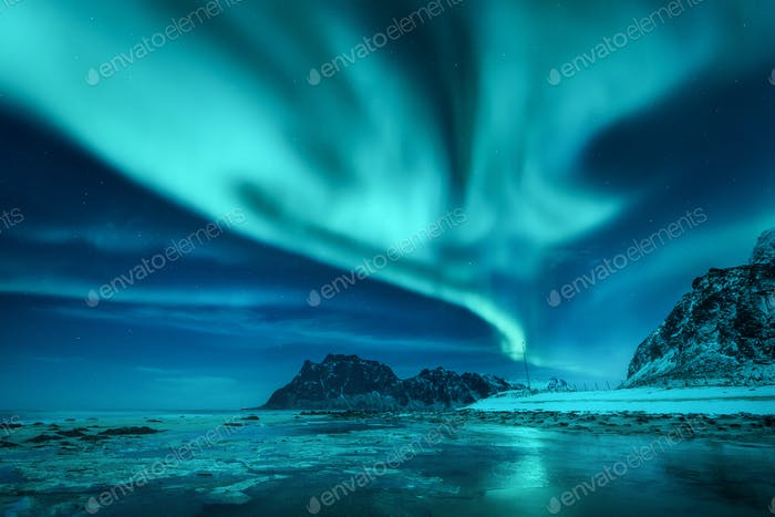Aurora borealis over the snowy mountains and sandy beach