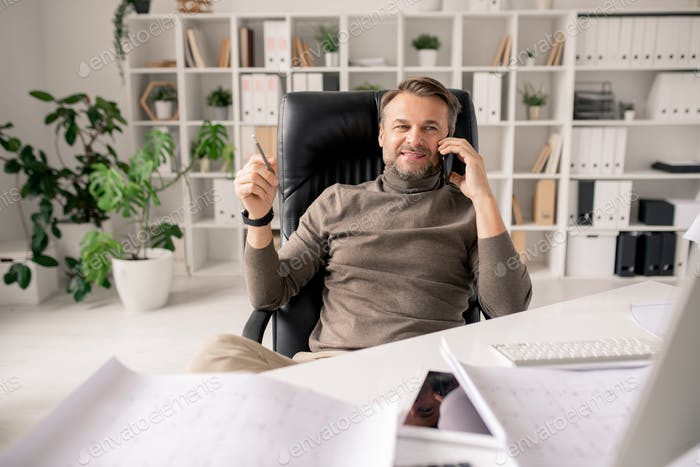 Fröhlicher reifer Architekt oder Geschäftsmann mit Smartphone im Gespräch mit Kunden