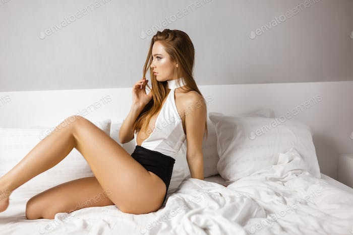 Young prettyl lady in black and white swimwear sitting in bed and dreamily looking aside