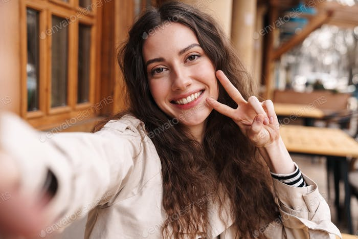 Image of happy woman taking selfie photo and gesturing peace